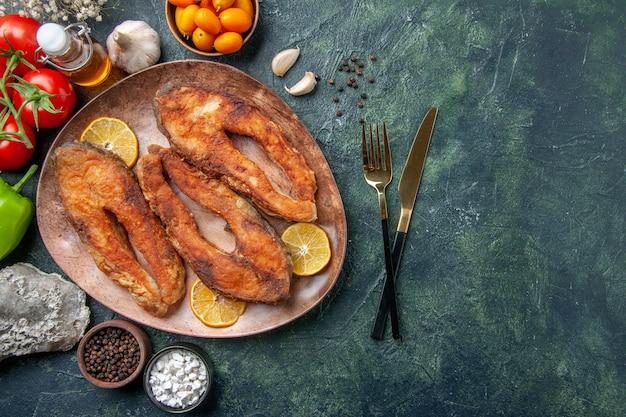 茶色のプレート上の揚げ魚とレモンスライスのビューの上に空きスペースのあるミックスカラーテーブルのスパイストマトオイルボトル