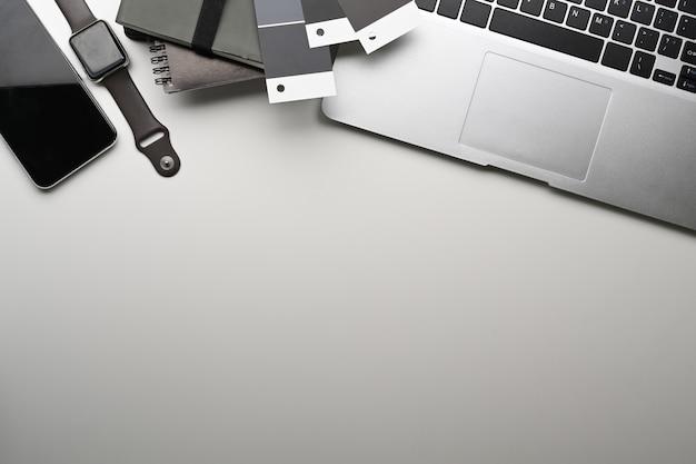 Выше вид рабочего места графического дизайнера с портативным компьютером, умными часами, умным телефоном и копией пространства на белом столе.