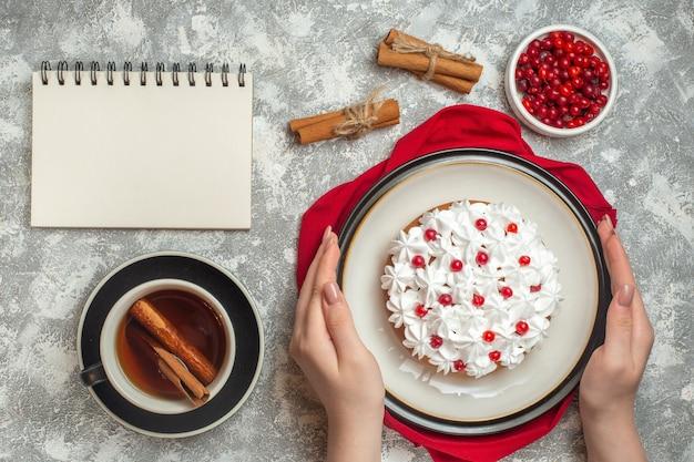 赤いタオルの上に果物で飾られたおいしいクリーミーなケーキを持っている手のビューの上