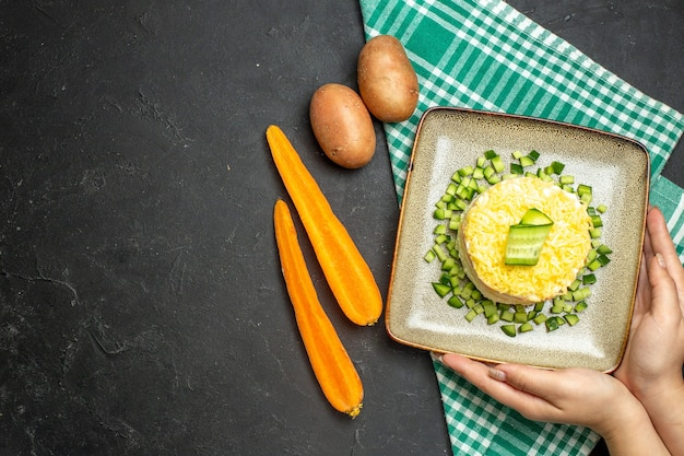 반으로 접힌 녹색 수건에 다진 오이와 어두운 배경에 당근 감자를 곁들인 맛있는 샐러드를 들고 있는 손의 위