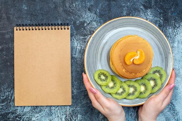 자연 요구르트로 만든 푹신한 미국식 팬케이크를 손에 들고 접시에 키위 과일과 귤과 함께 제공되고 얼음 배경에 여유 공간이 있는 노트북의 보기