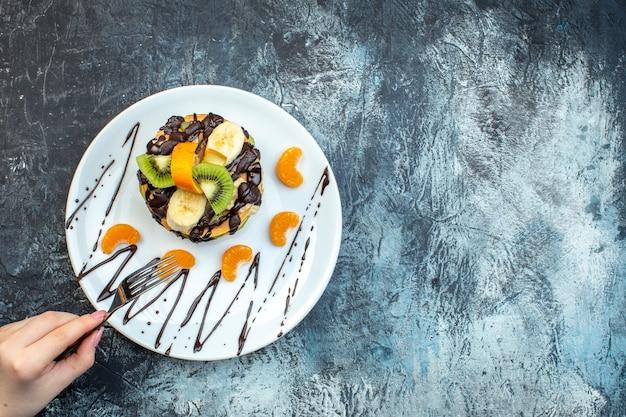 천연 요구르트로 만든 미국식 팬케이크에 포크를 들고 얼음 배경에 흰색 접시에 초콜릿으로 장식된 과일 겹을 쌓은 모습