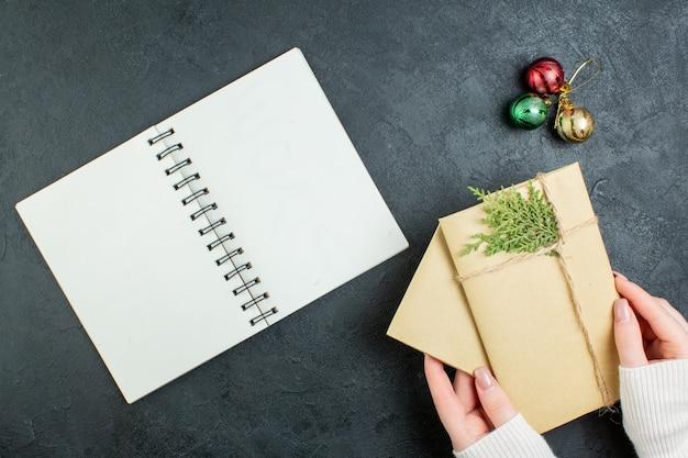 Выше вид руки, держащей подарочные коробки и аксессуары для украшения рядом со спиральной записной книжкой на темном фоне