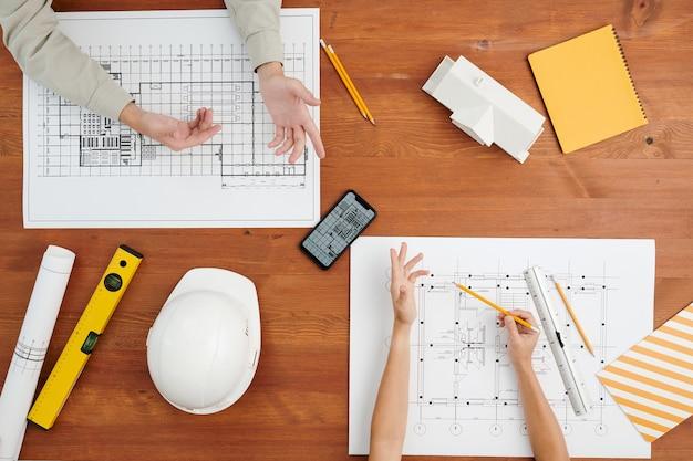 設計図のスケッチや変更可能なものについての新しいアイデアについて話し合う際の、クリエイティブアーキテクトの手のビューの上