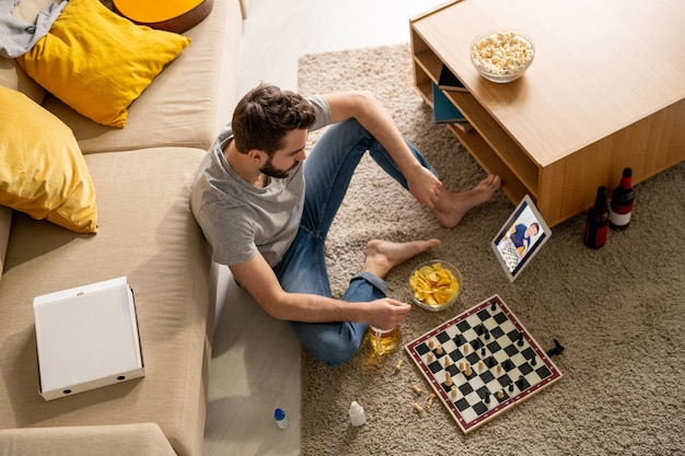 Вид сверху на красивого мужчину, сидящего на полу с пивом и чипсами и играющего в шахматы с другом через видеочат