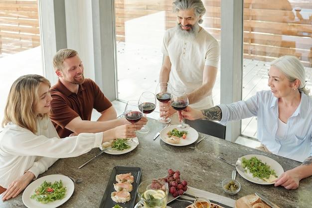 家族の夕食時にワイングラスをチリンと鳴らす幸せな先輩の両親とその年長の子供たちのビューの上
