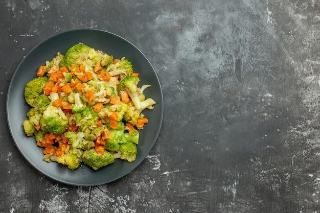 灰色のテーブルの上の黒いプレートにブロッコリーとニンジンと健康的な食事のビューの上