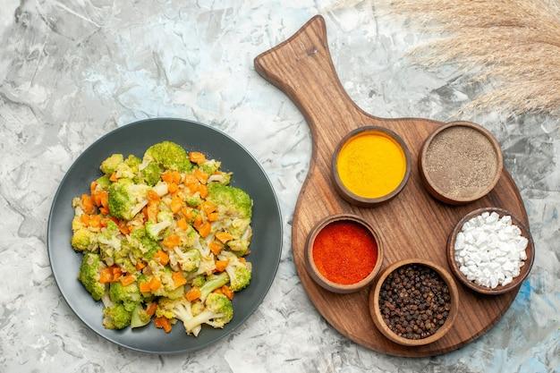 健康的な野菜サラダのビューの上に白いテーブルの上のさまざまなスパイスとまな板