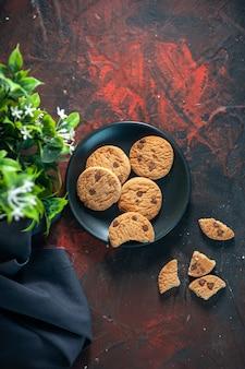 검은 접시에 있는 홈메이드 맛있는 설탕 쿠키와 어두운 혼합 색상 배경의 화분 위의 보기