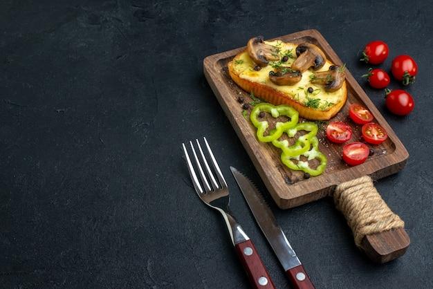 검은 배경에 놓인 나무 판자에 버섯과 다진 야채를 곁들인 홈메이드 맛있는 스낵의 전망