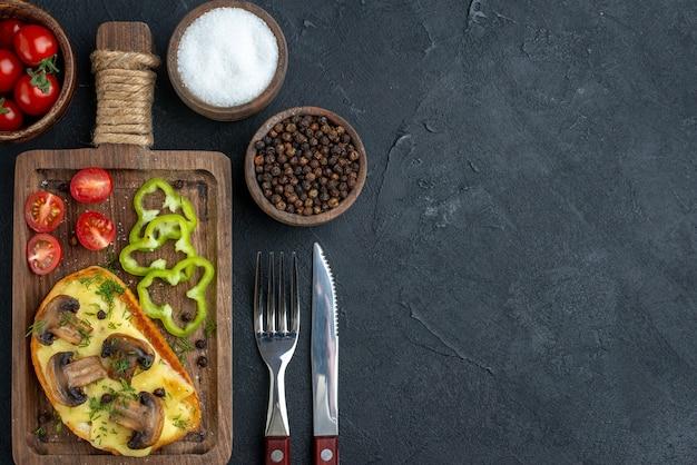 버섯과 잘게 썬 야채를 나무 판자에 얹은 홈메이드 맛있는 간식의 전망 위에는 검은 배경에 향신료가 놓여 있습니다