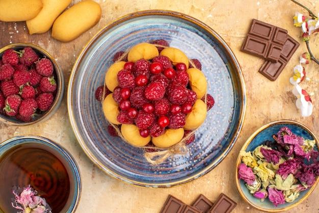 Выше вид мягкого торта горячего травяного чая с фруктами и шоколадными батончиками на столе смешанного цвета