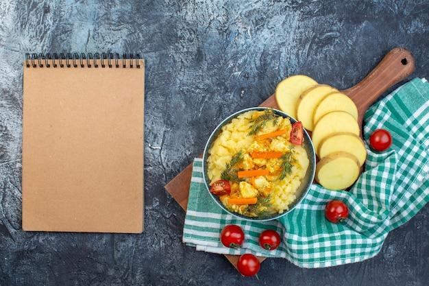 Выше вид картофельного пюре с укропом и свежими овощами на зеленом полосатом полотенце на деревянной доске и блокноте на темном фоне
