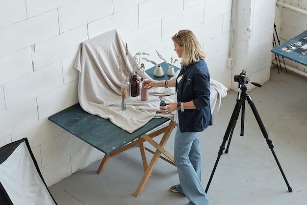 Вид сверху зрелого фотографа, создающего композицию из ваз и цветов на серой ткани.