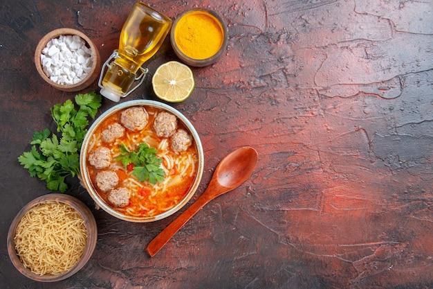 茶色のボウルレモンスプーンの麺とミートボールスープのビューの上に暗いテーブルの上の緑と油のボトルの束ストックイメージ