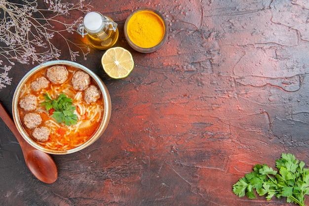 茶色のボウルレモンスプーンの麺とミートボールスープのビューの上に暗いテーブルの上の緑と油のボトルの束