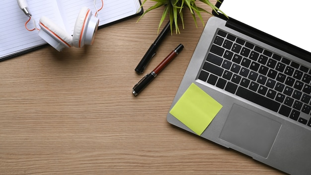목탁에 있는 컴퓨터 노트북, 헤드폰, 노트북, 펜, 식물을 조롱하는 모습.
