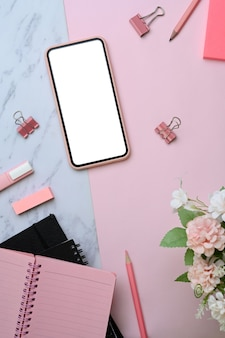 분홍색과 대리석 배경에 있는 모의 스마트폰과 사무용품의 보기.