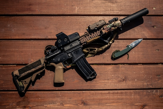 나무 탁자에 있는 현대적인 소총과 칼의 위, 군인 무기 개념