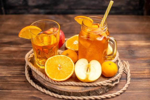 まな板の上にチューブと果物を添えた、ボトルとグラスに入った有機フレッシュ ジュースの写真の上