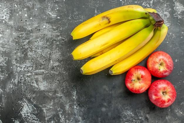 暗い背景の左側にある有機栄養源の新鮮なバナナの束と赤いリンゴのビューの上