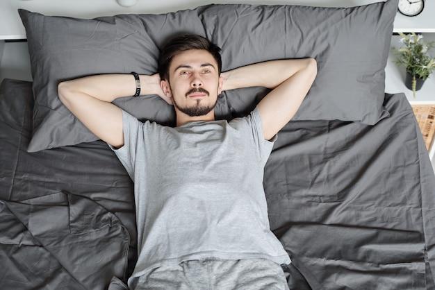 격리 기간 동안 침대에서 휴식을 취하는 동안 머리 뒤에 손을 잡고 잠겨있는 젊은 수염 난된 남자의보기 위