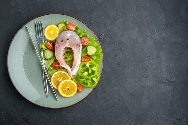 생선과 신선한 야채 레몬 조각과 칼 붙이는 여유 공간이있는 검은 색 표면의 왼쪽에 회색 접시에 설정되어 있습니다.