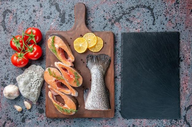 生の魚のビューの上にレモンスライスグリーンペッパー木製まな板と野菜カトラリーセット青黒色テーブルのダークカラートレイ