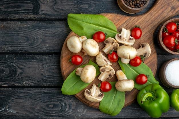 검정색 배경에 있는 나무 판자에 있는 생 버섯과 토마토 향신료의 보기 위