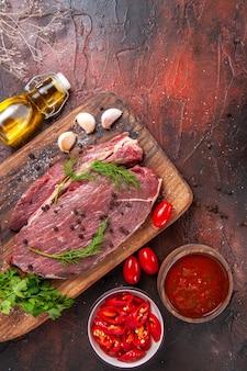 나무 커팅 보드에 있는 붉은 고기와 어두운 배경에 마늘 녹색 다진 페퍼 떨어진 오일 병 케첩의 보기