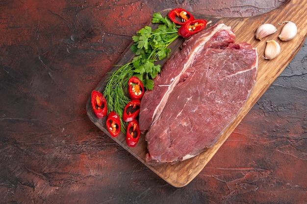 Выше вид красного мяса на деревянной разделочной доске и чесночного зеленого нарезанного перца на темном фоне