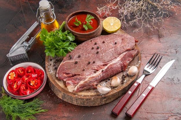 나무 쟁반에 있는 붉은 고기, 녹색 마늘 케첩, 어두운 배경에 잘게 썬 후추 기름 병