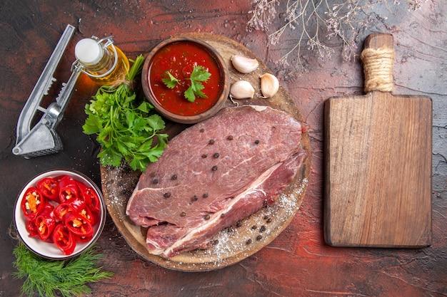Выше вид красного мяса на деревянном подносе и чесночного зеленого кетчупа и бутылки масла нарезанного перца на темном фоне