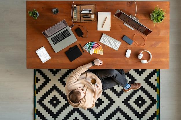 Выше вид расслабленного дизайнера в очках, сидящего за столом с дизайнерскими устройствами и пьющего кофе