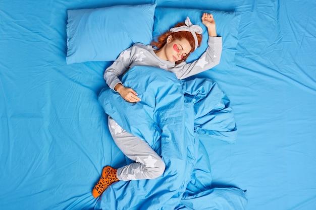 잠옷 머리띠를 입은 편안한 빨간 머리 여자의 위보기는 편안한 침대에서 부기를 줄이기 위해 눈 아래에 아름다움 패치를 적용하여 집에서 게으른 느낌을줍니다. 평화로운 분위기
