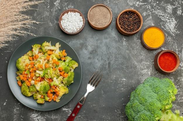 Выше вид набора различных специй в коричневых мисках и овощном салате со свежей брокколи