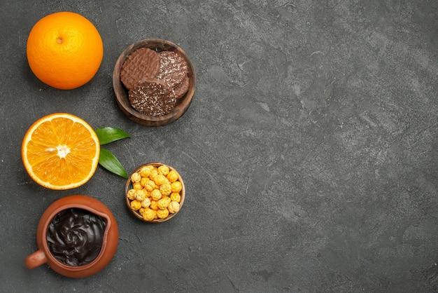 Выше вид набора целых и разрезанных пополам свежих апельсинов и печенья на темном столе