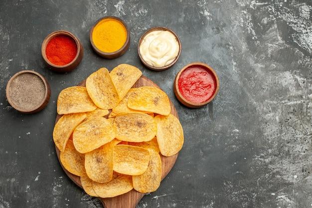 회색 테이블에 다른 향신료 마요네즈와 케첩을 포함하는 세트 감자 칩의 위보기