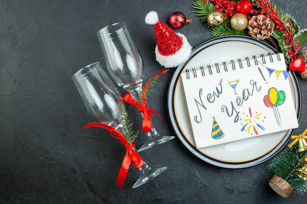 ディナープレートにペンでスパイラルノートの上のビュークリスマスツリーモミの枝針葉樹の円錐形のギフトボックスサンタクロースの帽子黒の背景に落ちたガラスのゴブレット