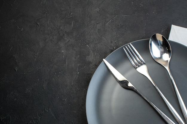 어두운 색 배경의 왼쪽에 있는 검은색 접시에 있는 스테인리스 칼 붙이의 보기 위