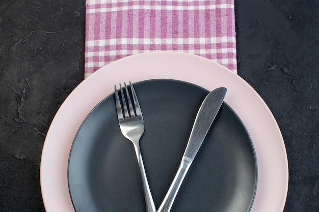 여유 공간이 있는 검정색 배경에 분홍색 벗겨진 수건에 있는 다채로운 세라믹 빈 접시에 놓인 스테인리스 칼붙이의 보기