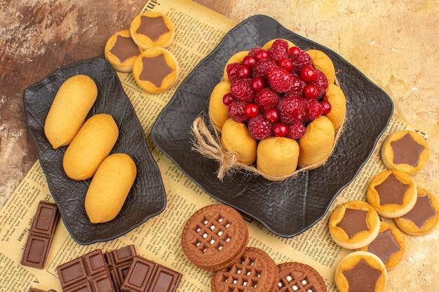 混合色のテーブルの茶色のプレート上のおいしいケーキのさまざまなビスケットのビューの上