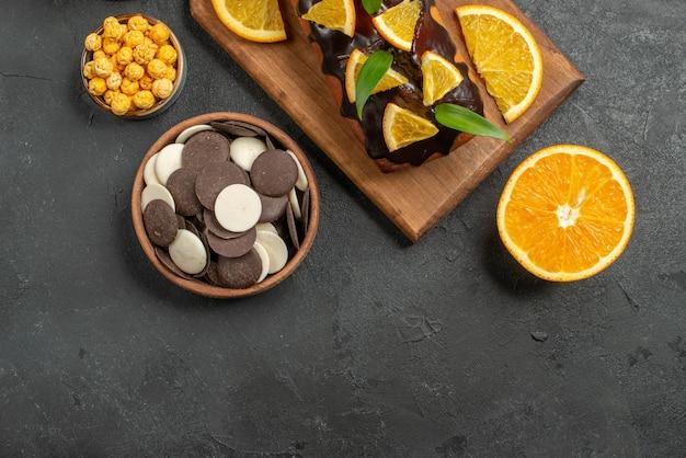 Выше вид вкусных тортов нарезанных апельсинов с печеньем на разделочной доске на темном столе