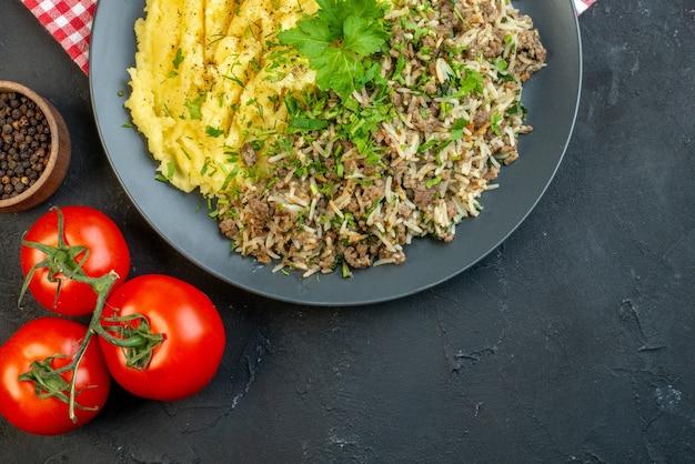 접시에 고기 으깬 감자를 곁들인 맛있는 저녁 식사와 여유 공간이 있는 검은 배경에 떨어진 기름병 후추 줄기가 있는 토마토