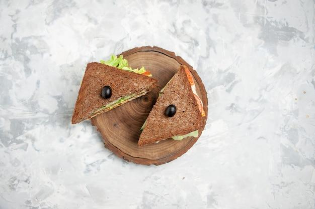 여유 공간이있는 스테인드 흰색 표면에 나무 커팅 보드에 올리브로 장식 된 검은 빵과 함께 맛있는 샌드위치보기 위