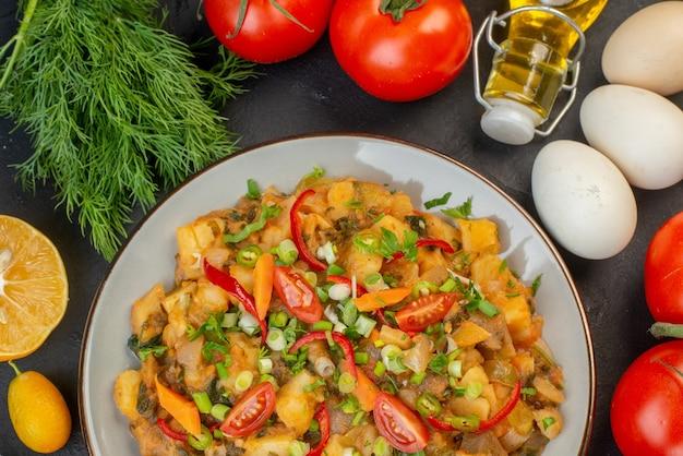 맛있는 채식주의 식단의 보기 위에 신선한 야채가 검은 배경에 떨어진 기름병 달걀