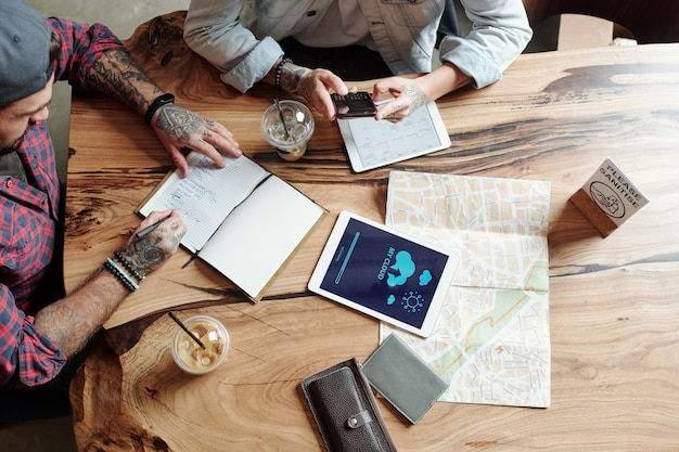 Выше вид татуированного мужчины, делающего заметки в планировщике во время подготовки к путешествию с другом в кафе