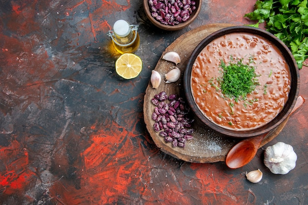 木製のまな板とオイルボトルレモングリーンのトマト石鹸豆にんにくスプーンのビューの上