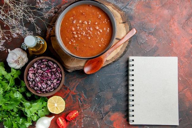 スプーン豆オイルボトルニンニクと混合色のテーブルのノートと木製のトレイに青いボウルのトマトスープの上のビュー