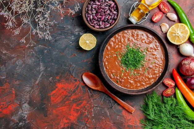 混合色のテーブルの上のトマトスープオイルボトル豆レモンと緑の束のビューの上